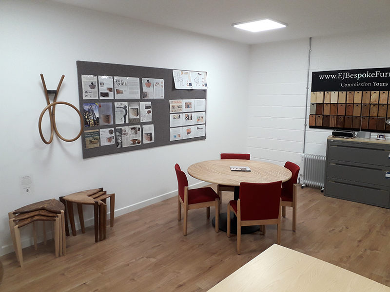 Inside of the new office showing meeting table, furniture and wood samples board on the wall.