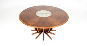 An extending dining table made from walnut and oak with a fabric and glass laminated centre.