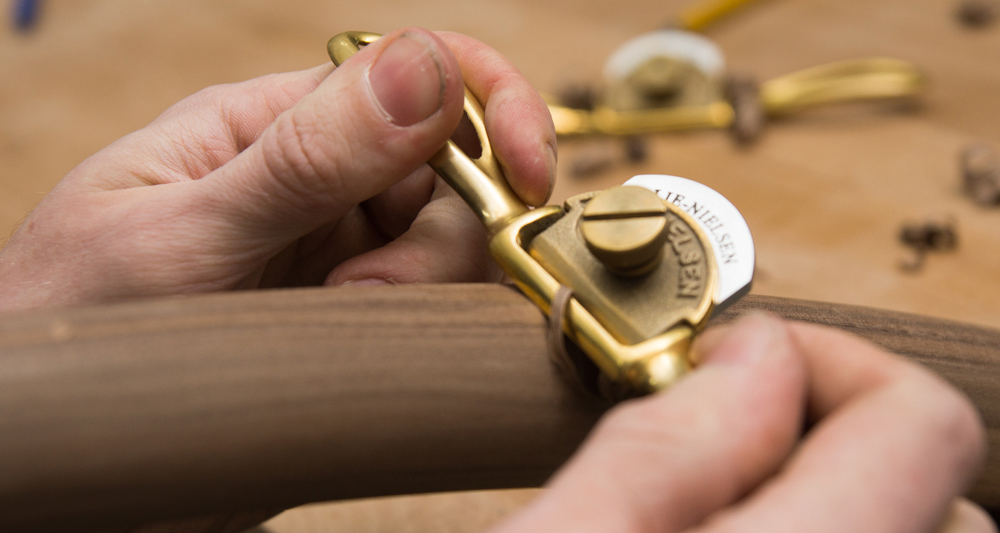 Hands using a traditional spokeshave in the workshop to carve timber.