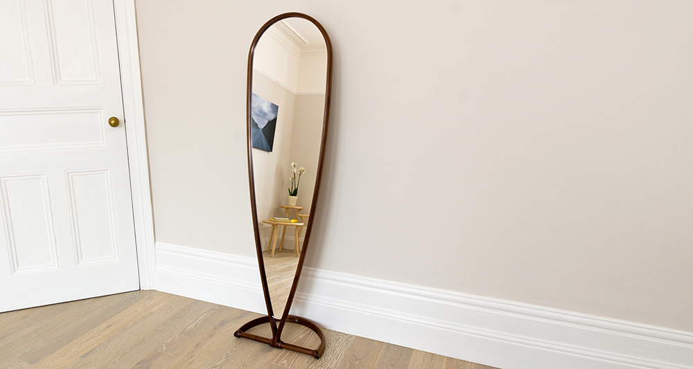 Our inverted teardrop-shaped full-length mirror with a walnut frame shown in a room setting