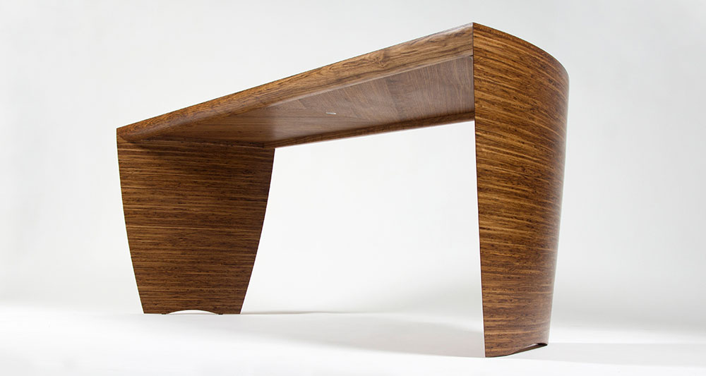 A view showing the sculptural legs and underside of the fumed oak and brown oak desk.