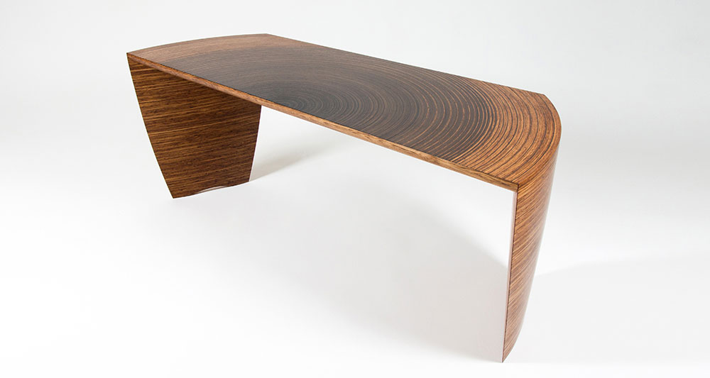 Radiant desk showing our curved Murano veneers. The top of the desk is reminiscent of the annual growth rings of a tree.