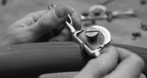 Hands using a traditional spoke-shave