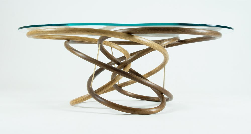 Side view of our Clover coffee table. The three legs are made from curved oak and fumed oak and intermingle around each other in a continuous loop. The table has a glass top.