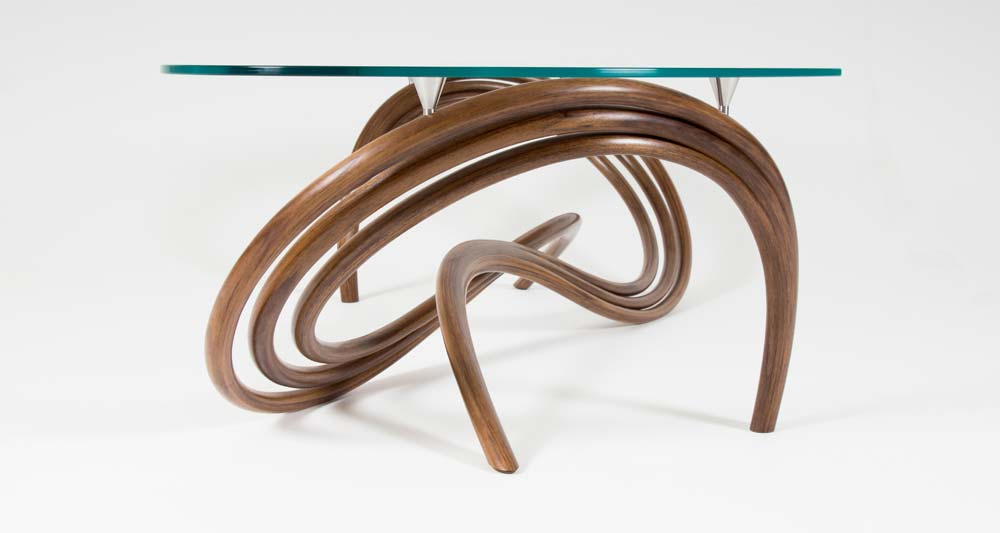 Ligamentum coffee table. The base is made of curving and intertwining legs made in walnut with a glass top.