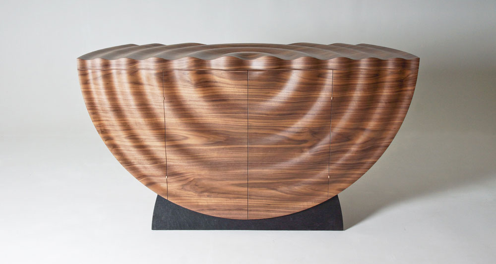 Front view of our Orbis rippled drinks cabinet made in walnut with oak interior.
