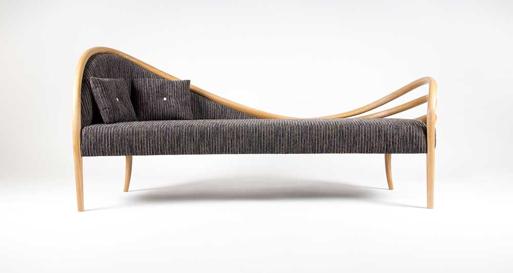 Front view of our Ligamentum III chaise longue with an asymmetrical design. Made from curved oak frame and legs with fabric upholstery.
