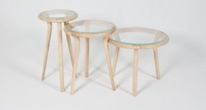 Set of three side tables displayed in a row, made from ash with glass tops. Designed at three different heights and diameters.