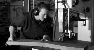 Edward in his workshop using a bandsaw cutting timber.
