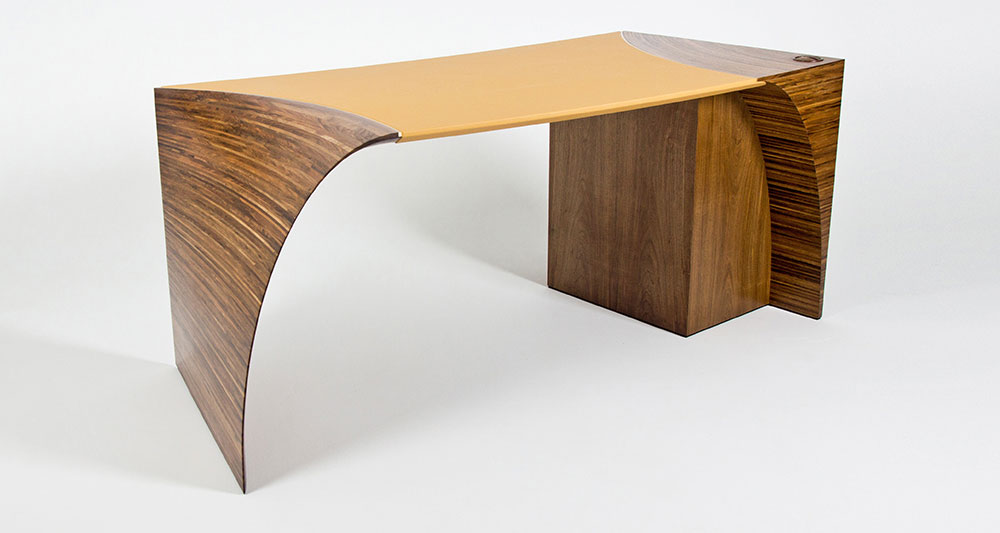 Three-quarter view of the Radium III desk made in walnut with deep yellow leather top.