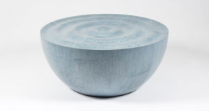 Domed blue bird's-eye maple coffee table with rippled surface shown without its glass top.