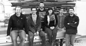 The Edward Johnson team sitting on the dim saw in the workshop.