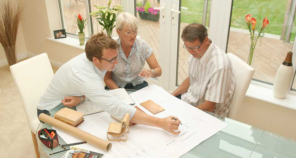 Commissioning our furniture: Edward Johnson sat at table with clients discussing the designs for their bespoke furniture.