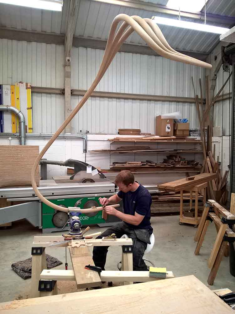 Edward Johnson in the workshop hand spoke-shaving the fram of a freeform chaise longue.
