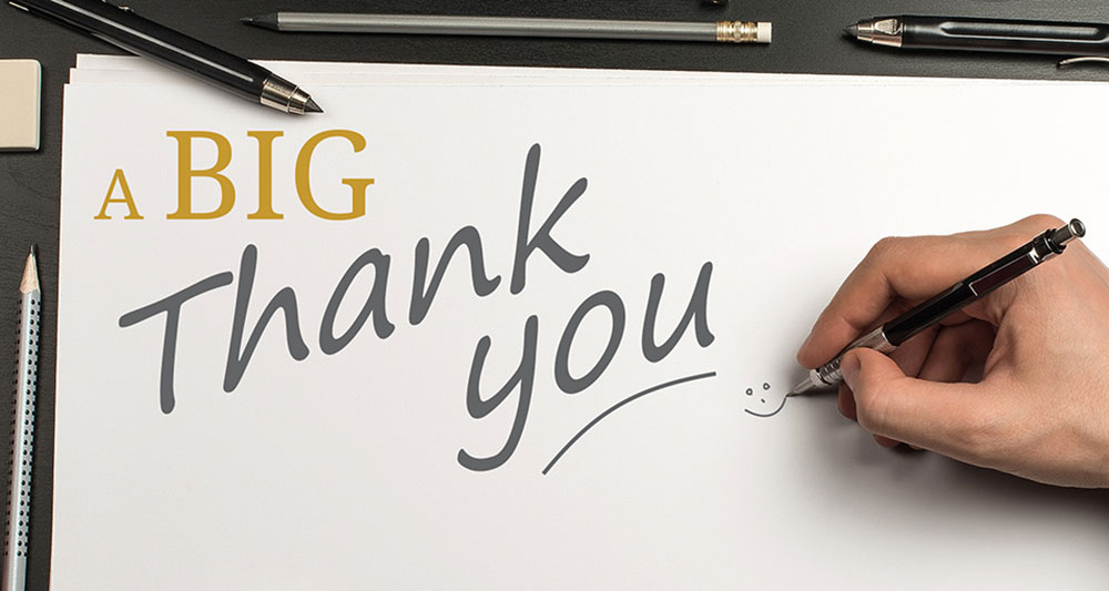 A heart-felt thank you to all our clients: written onto a large piece of paper. Shows a hand holding a pen.